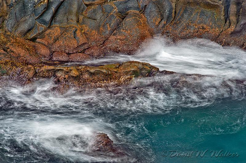 Waves crashing against volcanic rock at shoreline