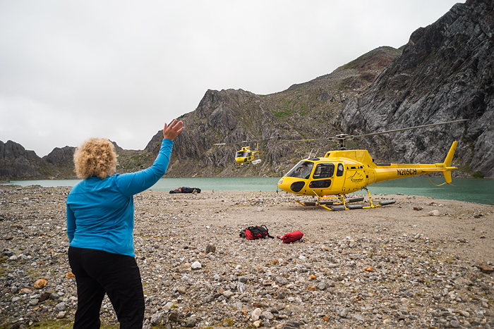 Woman waves goodbye to helicopter at beginning of a trekking adventure on Lemon